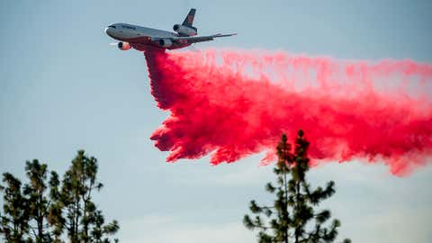 A DC-10 air tanker drops retardant while battling the Salt Fire near the Lakehead community in Shasta County, California, on July 2, 2021. (AP Photo/Noah Berger)