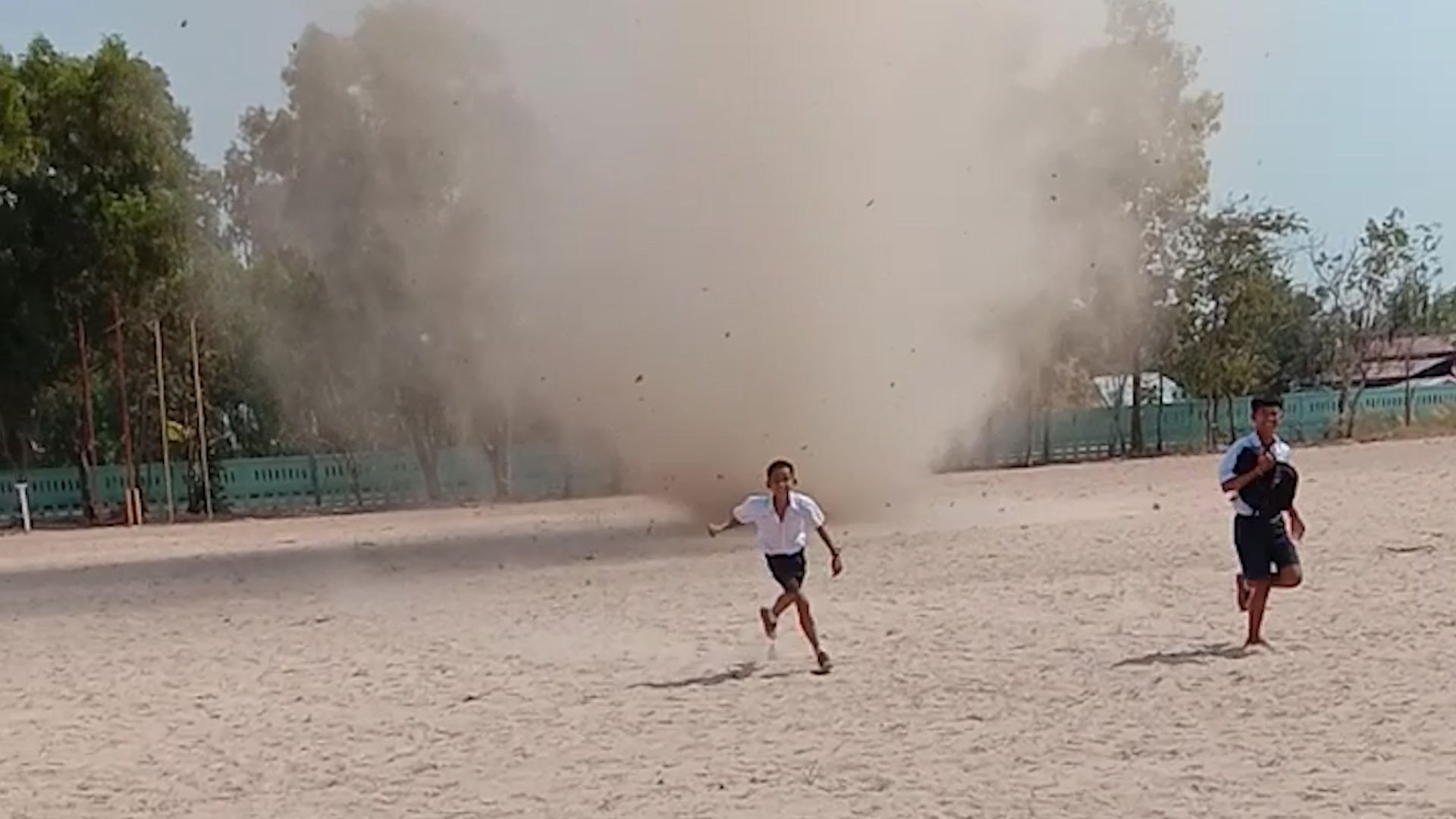 Students in Thailand Scurry as Dust Devil Winds Through Field