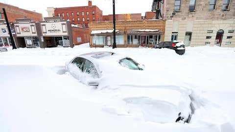 A car sits buried in snow on West 17th Street in downtown Cheyenne, Wyoming, on Monday, March 15, 2021. (Michael Cummo/Wyoming Tribune Eagle via AP)