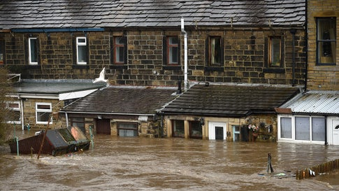 Flooded houses are pictured in Mytholmroyd, northern England, on Sunday, February 9, 2020, after the River Calder burst its banks as Storm Ciara swept over the country. (Photo by OLI SCARFF/AFP via Getty Images)