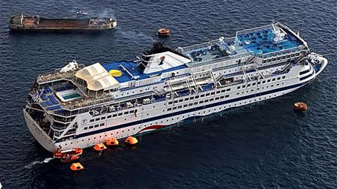 The listing cruise ship Sea Diamond  is surrounded by smaller ships during its evacuation effort off the coast of Santorini, Greece, on April 5, 2007. 05 April 2007. The 472-foot boat operated by Cyprus-based Louis Hellenic Cruises ran aground on a rocky coast one nautical mile off the shores of Santorini in the Aegean Sea. (STR/AFP via Getty Images)