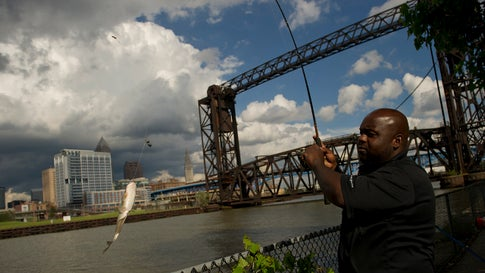 Tommy Greer fishes in the Cuyahoga River in Cleveland, Ohio, on July 8, 2014. Federal environmental regulators say fish living in the river that became synonymous with pollution when it caught fire in 1969 are now safe to eat. (Jeff Swensen/Getty Images)
