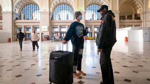 A traveler talks with a security officer at Washington Union Station, a major transportation hub in the nation's capital, Monday, March 16, 2020. The train station was nearly empty during morning rush hour as many government and private sector workers stay home during the coronavirus outbreak. (AP Photo/J. Scott Applewhite)