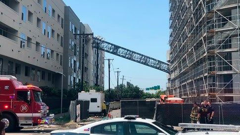 Officials respond to the scene after a crane collapsed into Elan City Lights apartments in Dallas amid severe thunderstorms on Sunday, June 9, 2019. (Michael Santana via AP)