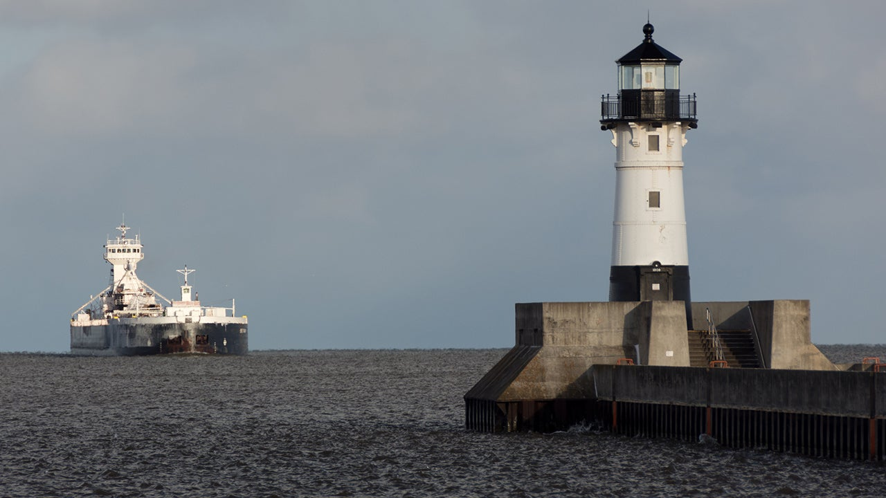 A tug pulls a barge toward the Duluth North Pier Light on Lake Superior in Duluth, Minnesota. A U.S. Army Corps of Engineers forecast says Lake Superior could reach record levels in the coming months. (Pete Markham/flickr)