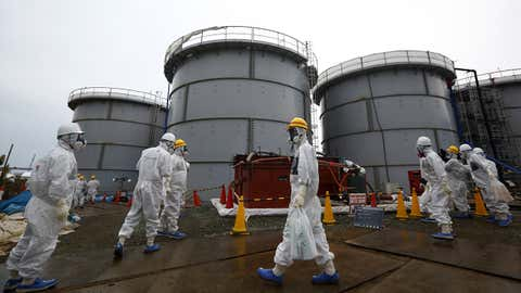 Members of the media and Tokyo Electric Power Co. employees wearing protective suits and masks walk past storage tanks for radioactive water at the Fukushima Daiichi nuclear power plant in Okuma, Fukushima Prefecture, Japan on November 7, 2013.  (TOMOHIRO OHSUMI/AFP via Getty Images)