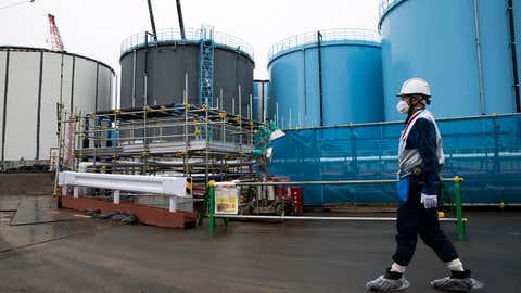 A Tokyo Electric Power Co.'s employee walks past storage tanks for contaminated water at the company's Fukushima Daiichi nuclear power plant in Okuma, Fukushima, Japan, on February 23, 2017. (TOMOHIRO OHSUMI/AFP via Getty Images)