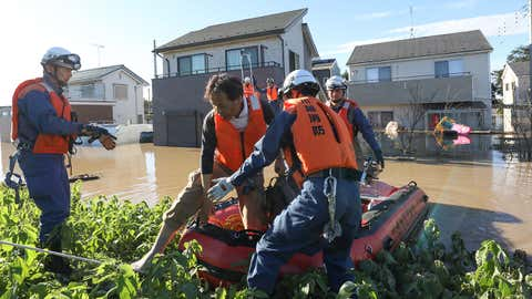 Fire department workers evacuate a resident from a flooded area in Kawagoe, Saitama Prefecture, on Sunday, October 13, 2019, one day after Typhoon Hagibis swept through central and eastern Japan. (JIJI PRESS/AFP via Getty Images)