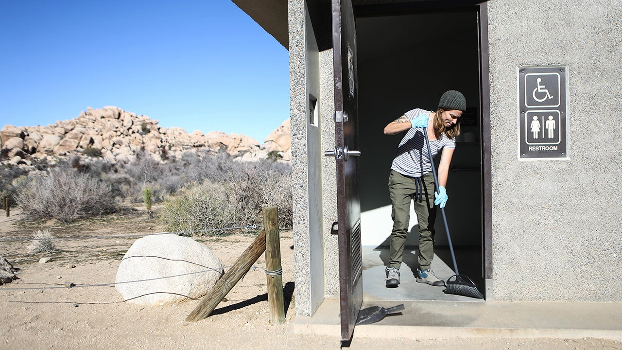 """Volunteer Alexandra Degen cleans a restroom at Joshua Tree National Park on Friday, January 4, 2019, in Joshua Tree National Park, California. Volunteers with """"Friends of Joshua Tree National Park"""" have been cleaning bathrooms and trash at the park as the park is drastically understaffed during the partial government shutdown. Campgrounds and some roads have been closed at the park because of safety concerns. (Mario Tama/Getty Images)"""