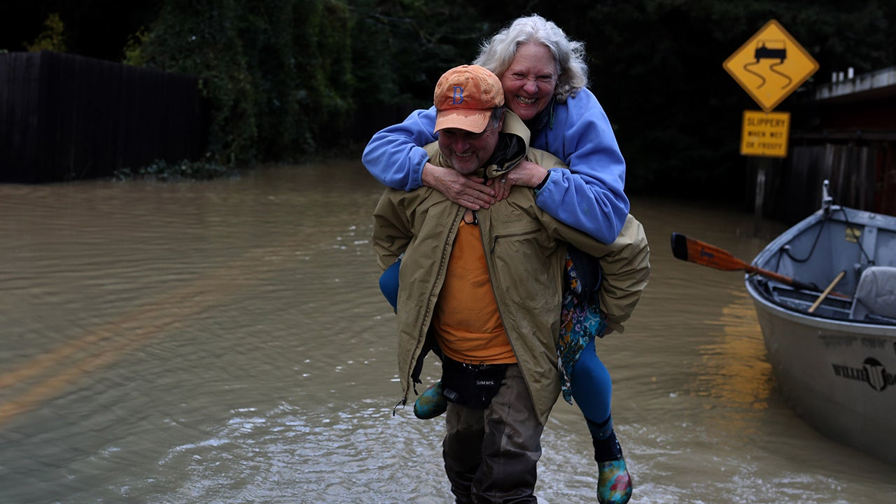 Bruce MacDonell carries Annie Lovell through floodwaters after using a boat to pass a flooded road on Feb. 15, 2019 in Guerneville, Calif. An atmospheric river is bringing heavy rains to Northern California that is causing rivers to overflow their banks and flood many areas around the Russian River. (Justin Sullivan/Getty Images)