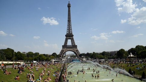 TOPSHOT - People cool off and sunbathe by the Trocadero Fountains next to the Eiffel Tower in Paris, on July 25, 2019 as a new heatwave hits the French capital. - After all-time temperature records were smashed in Belgium, Germany and the Netherlands on July 24, Britain and the French capital Paris could on July 25 to see their highest ever temperatures. (Photo by Bertrand GUAY / AFP)        (Photo credit should read BERTRAND GUAY/AFP/Getty Images)