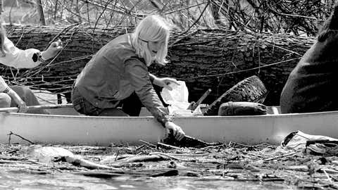 A woman picks trash out of the Potomac River on Earth Day in Washington, D.C., April 22, 1970. (Thomas J O'Halloran/U.S. News and World Report Collection/PhotoQuest/Getty Images)