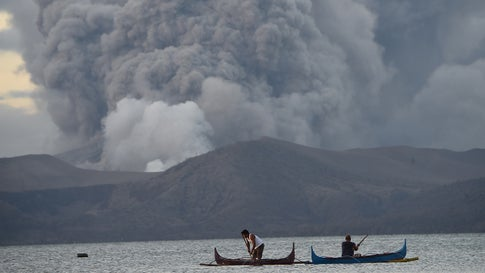 Residents living along Taal lake catch fish as Taal Volcano erupts in Tanauan town, Batangas province south of Manila on Tuesday, January 14, 2020. (Photo by Ted Aljibe/AFP via Getty Images)