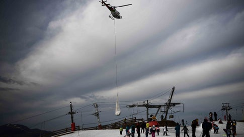 TOPSHOT - People look at an helicopter carrying snow in order to place it on a ski slope in the Superbagneres station, near Luchon, in French Pyrenees mountain southwestern France, on February 15, 2020. - The French department of Haute-Garonne decided to pour snow by helicopter on the Luchon-Superbagneres station in order to make up for the lack of snow on February 14 and February 15, 2020. (Photo by Anne-Christine POUJOULAT / AFP) (Photo by ANNE-CHRISTINE POUJOULAT/AFP via Getty Images)