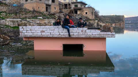Young Kurdish boys picnic on a building of the ancient city of Hasankeyf which will soon be under water as part of a controversial dam project, on February 24, 2020. - Despite years of protests by residents and activists, the small village on the banks of the Tigris River will soon be underwater as part of a controversial dam project. Authorities have started to move some historic monuments, and have already destroyed others. Old city has been abandoned, government cut electricity and water, the historic market, has been destroyed and disappear during last days. Residents are being moved from the ancient town to a 'New Hasankeyf' nearby, while historic artefacts have also been transported out of the area. (Photo by BULENT KILIC/AFP via Getty Images)
