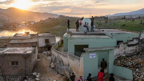 People visit abandoned houses of the ancient city of Hasankeyf which will soon be underwater as part of a controversial dam project, on February 24, 2020. Despite years of protests by residents and activists, the small village on the banks of the Tigris River will soon be underwater as part of a controversial dam project. Authorities have started to move some historic monuments, and have already destroyed others. Old city has been abandoned, government cut electricity and water, the historic market, has been destroyed and disappear during last days. Residents are being moved from the ancient town to a 'New Hasankeyf' nearby, while historic artefacts have also been transported out of the area. (Photo by BULENT KILIC/AFP via Getty Images)