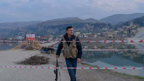 A Kurdish village guard waits to block the entrance to the ancient city of Hasankeyf which will be soon under water as part of a controversial dam project, on February 24, 2020. Despite years of protests by residents and activists, the small village on the banks of the Tigris River will soon be underwater as part of a controversial dam project. Authorities have started to move some historic monuments, and have already destroyed others. Old city has been abandoned, government cut electricity and water, the historic market, has been destroyed and disappear during last days. Residents are being moved from the ancient town to a 'New Hasankeyf' nearby, while historic artefacts have also been transported out of the area. (Photo by BULENT KILIC/AFP via Getty Images)