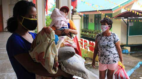 Residents carrying their belongings and wearing face masks, arrive at a school compound serving as temporary shelter in Sorsogon town, Bicol region, south of Manila on May 14, 2020, as Typhoon Vongfong approaches. - A powerful typhoon hit the central Philippines on May 14, forcing a complicated and risky evacuation for tens of thousands already hunkered down at home during the coronavirus pandemic. Because of the twin threat of the storm and the virus, evacuation centres in the central Philippines will only accept half their capacity and evacuees will have to wear facemasks. (Photo by Sharbyn SAYAT / AFP) (Photo by SHARBYN SAYAT/AFP via Getty Images)