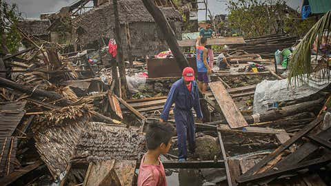 Residents try to salvage belongings amongst their houses destroyed at the height of Typhoon Vongfong in San Policarpo town, Eastern Samar province on May 15, 2020, a day after the typhoon hit the town. - Typhoon Vongfong has dumped heavy rains and torn off roofs since it roared ashore on central Samar island on May 14, with hundreds of thousands of vulnerable people in its path on the coast or in flimsy homes. (Photo by Alren BERONIO / AFP) / The erroneous mention[s] appearing in the metadata of this photo by Alren BERONIO has been modified in AFP systems in the following manner: [San Policarpo] instead of [San Policarpio]. Please immediately remove the erroneous mention[s] from all your online services and delete it (them) from your servers. If you have been authorized by AFP to distribute it (them) to third parties, please ensure that the same actions are carried out by them. Failure to promptly comply with these instructions will entail liability on your part for any continued or post notification usage. Therefore we thank you very much for all your attention and prompt action. We are sorry for the inconvenience this notification may cause and remain at your disposal for any further information you may require. (Photo by ALREN BERONIO/AFP via Getty Images)