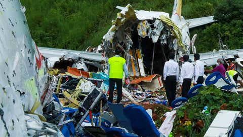 TOPSHOT - Officials inspect the wreckage of an Air India Express jet at Calicut International Airport in Karipur, Kerala, on August 8, 2020. - Fierce rain and winds lashed a plane carrying 190 people before it crash-landed and tore in two at an airport in southern India, killing at least 18 people and injuring scores more, officials said on August 8. (Photo by Arunchandra BOSE / AFP) (Photo by ARUNCHANDRA BOSE/AFP via Getty Images)