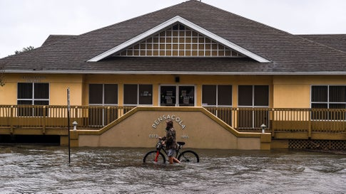 """A man walks with his bicycle through a street flooded by rains from Hurricane Sally in downtown Pensacola, Fla., on Sept. 16, 2020. Hurricane Sally barreled into the Gulf Coast early Wednesday, with forecasts of drenching rains that could provoke """"historic"""" and potentially deadly flash floods.The National Hurricane Center (NHC) said the Category 2 storm hit Gulf Shores, Ala., at about 4:45 a.m., bringing maximum sustained winds of about 105 miles per hour. """"Historic life-threatening flooding likely along portions of the northern Gulf coast,"""" the Miami-based center had warned late Tuesday, adding the hurricane could dump up to 20 inches of rain in some areas. (Chandan Khanna/AFP via Getty Images)"""