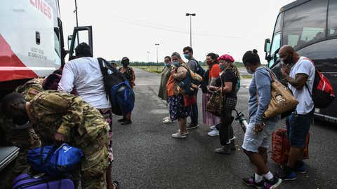 People line up to board a bus for evacuation before the arrival of hurricane Delta in Lake Charles, Louisiana on October 8, 2020. - Hurricane Delta gained strength October 8, 2020, as it churned across the western Gulf of Mexico towards the United States, threatening to batter part of the Louisiana coast still recovering from a separate storm just weeks ago. (Photo by CHANDAN KHANNA / AFP) (Photo by CHANDAN KHANNA/AFP via Getty Images)