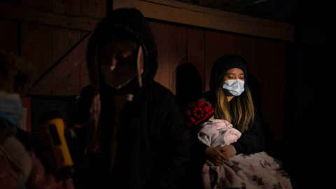 HOUSTON, TX - FEBRUARY 18: Surrounded by tarp and bedsheets, Evelyn Hernandez, 15, and her sister, Daeslyn Hernandez, 1, keep warm by the glow of a camping stove on their familys front porch following an unprecedented winter storm in Houston, Texas on February 18, 2021. The Hernandez family lost power on Monday morning and are preparing for another deep freeze.  (Photo by Callaghan OHare for The Washington Post via Getty Images)