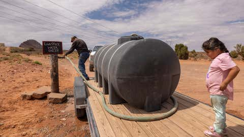 TUBA CITY, AZ - JULY 4: Nate fills a water tank intended for drought-affected livestock from a community rancher's well on the Navajo Nation on July 4, 2021 south of Tuba City, Arizona. Large portions of the West are now classified as being in exceptional drought, the most extreme drought category. Many major reservoirs have reached historic low levels and fire officials are warning that another devastating wildfire season has already begun.   (Photo by David McNew/Getty Images)
