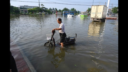 A man rides a motorcycle on a flooded road after heavy rain in Xinxiang, in central Chinas Henan province on July 23, 2021. (Jade Gao/AFP via Getty Images)