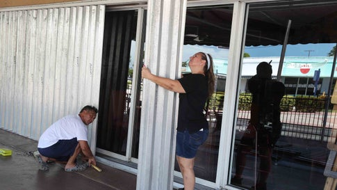 STUART, FLORIDA - AUGUST 01: David Terrazas and Andrea Hagopian (L-R) put shutters over the sliding glass doors at Maria's Restaurant as Hurricane Isaias approaches on August 01, 2020 in Stuart, Florida. The hurricane is expected to brush past the east coast of Florida within the next 24 hours. (Photo by Joe Raedle/Getty Images)
