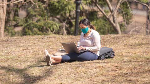 NEW YORK, NEW YORK - MARCH 23: A person works on her laptop in Central Park amid the coronavirus pandemic on March 23, 2021 in New York City. After undergoing various shutdown orders for the past 12 months the city is currently in phase 4 of its reopening plan, allowing for the reopening of low-risk outdoor activities, movie and television productions, indoor dining as well as the opening of movie theaters, all with capacity restrictions. (Photo by Noam Galai/Getty Images)