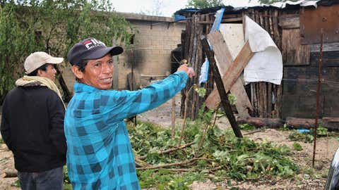 A resident points at his house that needed to be boarded up after Grace hit Tulum, Mexico, as a Category 1 hurricane on August 19, 2021. (Medios y Media/Getty Images)