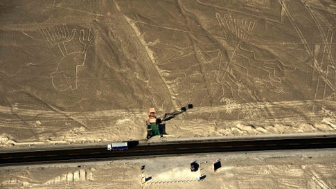 Aerial view of geoglyphs representating a guarango tree (R) and  hands, at Nazca Lines, some 435 km south of Lima, Peru on December 11, 2014. Geoglyphs can be seen only from atop the surrounding foothills or from aircrafts. The purpose of the Nazca lines remains unclear, according some scientists the Nazca people created them to be seen by their gods in the sky.The area of the Nazca Lines cover nearly 500 km2.      AFP PHOTO / MARTIN BERNETTI        (Photo credit should read MARTIN BERNETTI/AFP via Getty Images)