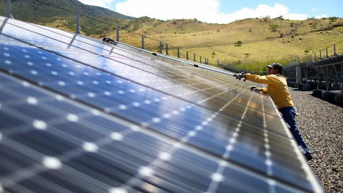 A worker cleans the panels in a solar power park run by the Costa Rican Electricity Institute in Guanacaste, Costa Rica, in 2015. This year, the power company produced all of the electricity for the nation from renewable energy sources for 300 days. ( Joe Raedle/Getty Images)