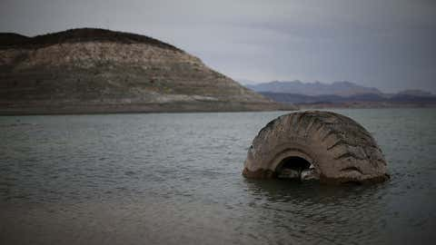 A tractor tire sits in the waters of Lake Mead, Nevada, near Boulder Beach on May 13, 2015. Once the largest reservoir in the nation, Lake Mead saw its surface elevation drop below 1,080 feet above sea level in 2015 and 2016, the lowest levels observed since the construction of the Hoover Dam in the 1930s. As of early 2019, the lake remained far below levels that prevailed in almost every year through the 1990s. (Photo by Justin Sullivan/Getty Images)