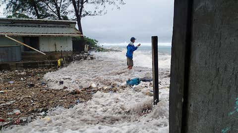 A resident of Majuro in the Marshall Islands is surrounded by the on-rushing high tide energized by a storm surge that damaged a number of homes across the island on March 3, 2014. It was the third inundation of the Marshall's capital atoll in 12 months. (Karl Fellenius/AFP/Getty Images)
