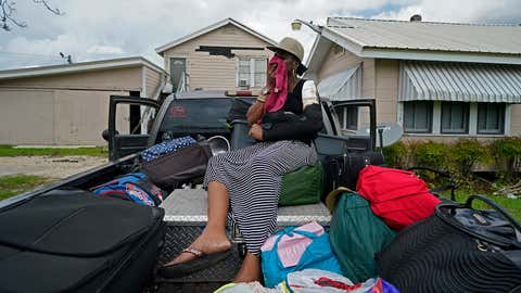 Rakisha Murray cries in relief as she arrives to see her mother's home largely undamaged on Sunday, August 30, 2020, after she returned from evacuation with her mother and other family in Lake Charles, Louisiana. (AP Photo/Gerald Herbert)