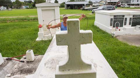 Jerry Parria uses steel cable and metal anchors to tie down four tombs belonging to his grandparents and uncles in a small cemetery near Lafitte, Louisiana, on Monday, August 24, 2020, as residents along the Louisiana coast prepare for Hurricane Laura. Parria said the tombs floated away during a previous hurricane. (Chris Granger/The Times-Picayune/The New Orleans Advocate via AP)