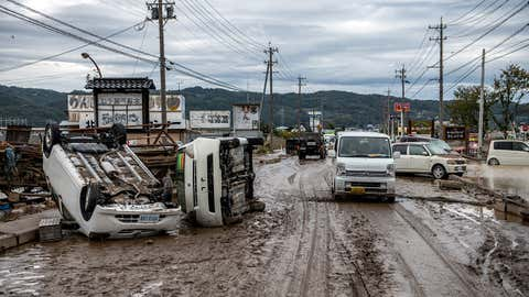 A car passes overturned vehicles in Nagano, Japan, on Monday, October 14, 2019, in an area affected by flooding after being hit by Typhoon Hagibis. (Carl Court/Getty Images)
