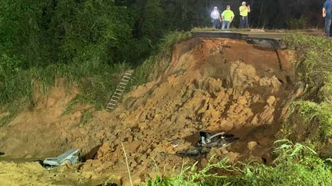 Emergency personnel look over the stretch of Highway 26 in George County, Mississippi, that collapsed Monday, August 30, 2021, during torrential rain caused by Tropical Storm Ida. Two people were dead and as many as 10 others were injured when the road collapsed, according to the Mississippi Highway Patrol.