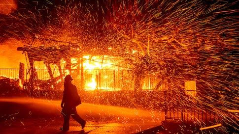 A firefighter passes a burning home as the Hillside Fire burns in San Bernardino, California, on Thursday, October 31, 2019. The blaze, which ignited during red flag fire danger warnings, destroyed multiple residences. (AP Photo/Noah Berger)