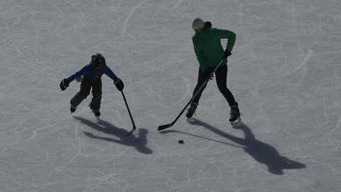LAKE LOUISE, CANADA - FEBRUARY 27: A mother and her son practice on an ice pad adjacent to outdoor shinny hockey action during the 7th Annual Lake Louise Pond Hockey Classic on the frozen surface of Lake Louise on February 27, 2016 in Lake Louise, Alberta, Canada. (Photo by Tom Szczerbowski/Getty Images)