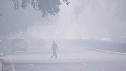 A man crosses a street in smoggy conditions in New Delhi on Monday, November 4, 2019. Millions of people in India's capital started the week choking through