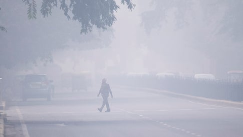 """A man crosses a street in smoggy conditions in New Delhi on Monday, November 4, 2019. Millions of people in India's capital started the week choking through """"eye-burning"""" smog, with schools closed, cars taken off the road and construction halted. (Jewel Samad/AFP via Getty Images)"""
