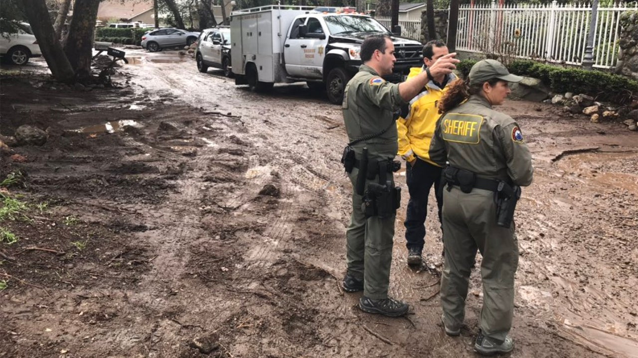 Members of the Los Angeles County Sheriff's Department, Malibu Search and Rescue and Los Angeles County Fire Department Search and Rescue look over a mud-covered street Sunday, February 3, 2019,  in Ramirez  Canyon in Malibu, California. (Los Angeles County Sheriff's Department)