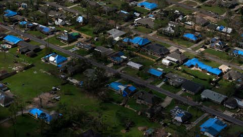 """Blue tarps cover the roofs of homes in Lake Charles, Louisiana, that were damaged after Hurricane Laura and Hurricane Delta. The city's mayor says, """"The plight of the average homeowner in Lake Charles is unthinkable at this moment."""" (Photo by Callaghan OHare for The Washington Post via Getty Images)"""