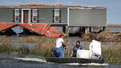Anthony Vincent and Mary Vincent use their boat to save food that they retrieved from a freezer in their home on Saturday, August 29, 2020, in Little Chenier, Louisiana. (Photo by Joe Raedle/Getty Images)