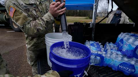 Mississippi Army National Guard Sgt. Chase Toussaint with the Maneuver Area Training Equipment Site of Camp Shelby, right, fills 5-gallon buckets with non-potable water, Monday, March 1, 2021, at a Jackson, Mississippi, water distribution site on the New Mt. Zion Missionary Baptist Church parking lot. Water for flushing toilets was being distributed at seven sites in Mississippi's capital city — more than 10 days after winter storms wreaked havoc on the city's water system because the system is still struggling to maintain consistent water pressure, authorities said. (AP Photo/Rogelio V. Solis)