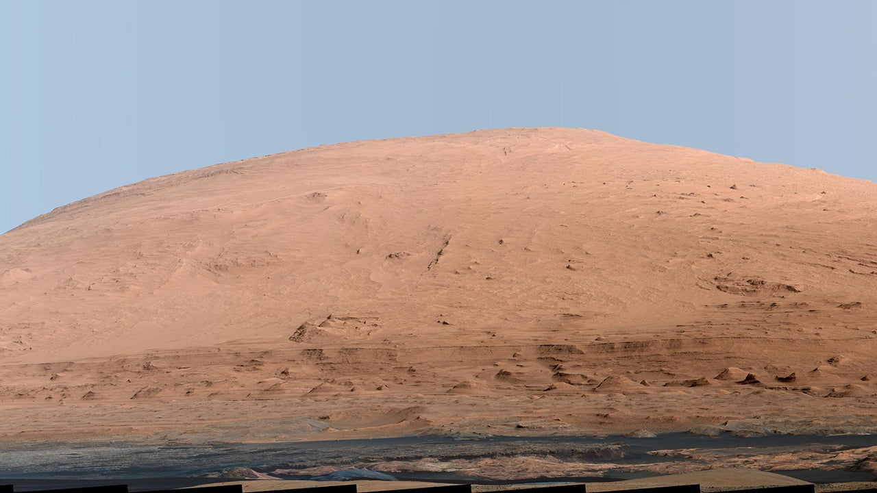 This mosaic of images from the Mast Camera (Mastcam) on NASA's Mars rover Curiosity shows Mount Sharp in a white-balanced color adjustment that makes the sky look overly blue but shows the terrain as if under Earth-like lighting. (NASA/JPL-Caltech/MSSS)