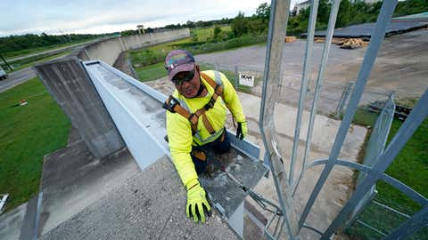 Joe Marshall of the Southeast Louisiana Flood Protection Authority - West secures a floodgate they just closed in Harvey, La., just outside New Orleans, Monday, Aug. 24, 2020, in advance of Hurricane Marco, expected to come near the Southern Louisiana coast. (AP Photo/Gerald Herbert)